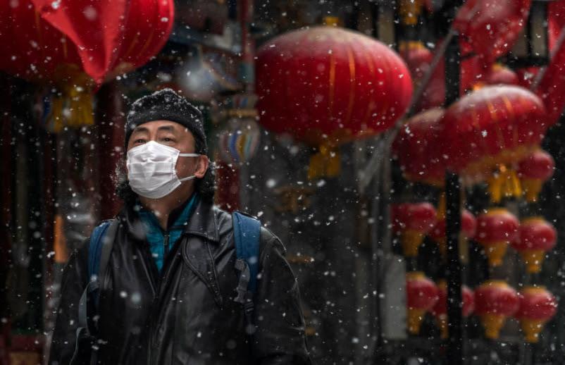 Un hombre chino usa una máscara protectora mientras camina durante una nevada en una calle comercial vacía y cerrada el 5 de febrero de 2020 en Beijing, China.