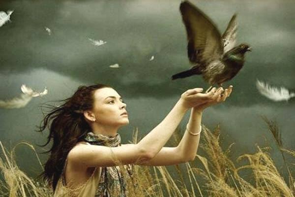 Mujer liberando una paloma de sus manos