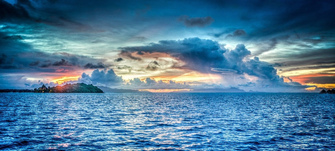 A veiw of the ocean from Bora Bora--blue sea, blue sky, dramatic clouds, orange and pinks of sunset, and twinkling lights of a distant village