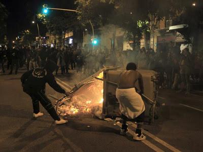 Dos personas colocan un contenedor incendiado en mitad de la calle. EFE/Toni Albir