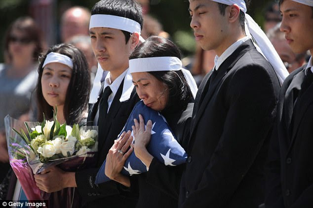 Myhanh Best, Ricky's wife, clutches the flag that draped his casket during a committal service on Monday