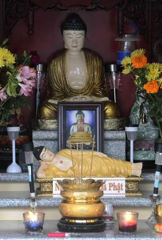 Images of Buddha are the centerpiece of an altar that grew around a single statue placed by a non- Buddhist. Photo: Paul Chinn, The Chronicle