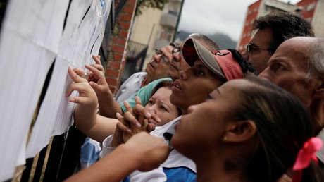 La gente consulta su nombre en una lista en un centro electoral durante las elecciones municipales del 10 diciembre de 2017 en Caracas, Venezuela.