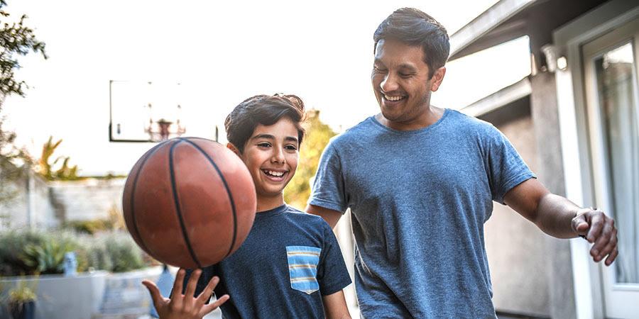 foto de un padre e un hijo jugando con una pelota de baloncesto