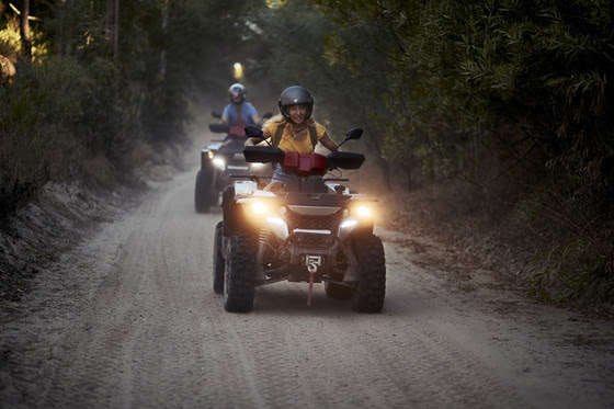 Two people riding two ATVs at dusk.