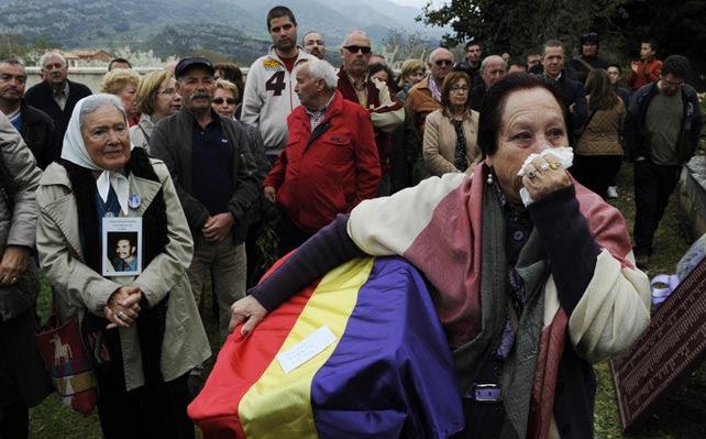 Juana Gutiérrez llora mientras mantiene los restos de su abuelo, víctima de la Guerra Civil, en el cementerio de Valdenoceda, cerca de Burgos.