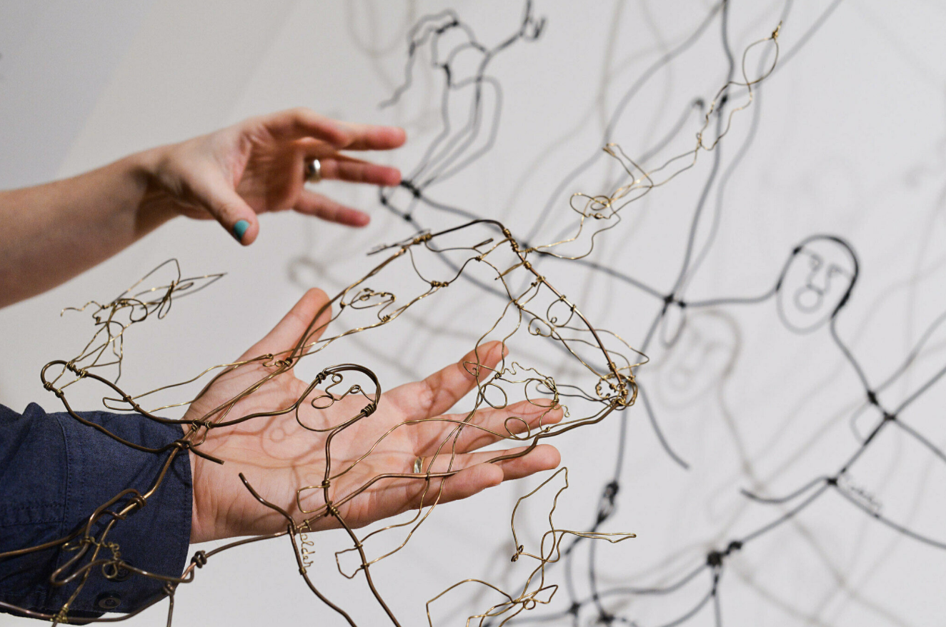 Hands hold a touch object of Alexander Calder's wire sculpture The Brass Family,