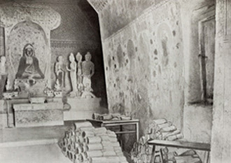 Cave 16 at the Buddhist caves near Dunhuang. The piles of scrolls and tables were probably added to the negative by the photographer, showing the empty cave after his original photograph of this scene was double exposed. Photograph, M. Aurel Stein, 1907 ©Ruins of Desert Cathay, Fig. 188.