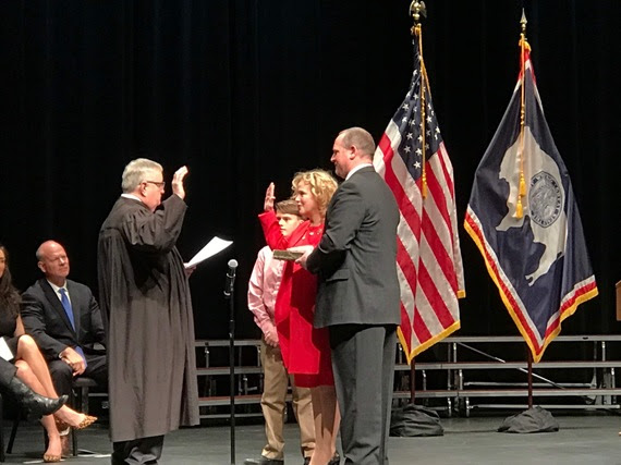 State Superintendent Jillian Balow holds up her right hand with her left hand on a bible held by her husband to take the Oath of Office from the Chief Justice of the Wyoming Supreme Court during the Swearing-In Ceremony at the Cheyenne Civic Center.