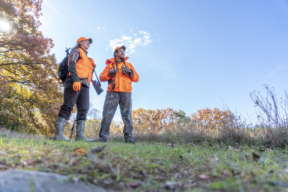 Two hunters stand together while out in the field.