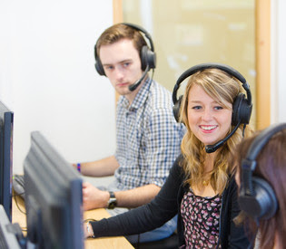 Image of 3 students with headsets on in a language lab.