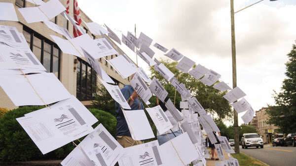 A rally outside the Montclair, N.J., town hall on July 1. Protesters hung 1,101 absentee ballots to represent the number of votes that weren't counted in a mayoral election that was decided by just 195 votes.