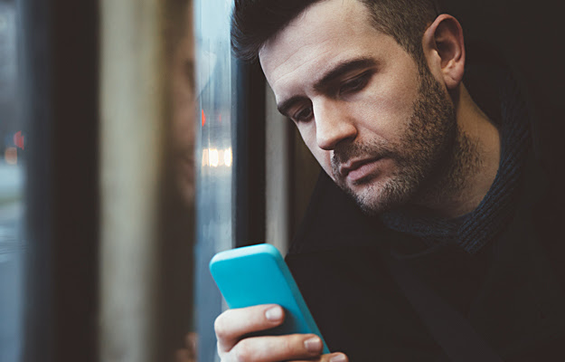 A man looking at his cell phone.