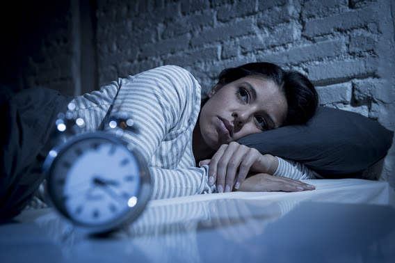 woman lying in bed with alarm clock