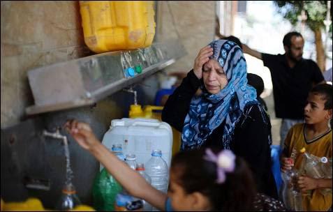 Los palestinos llenan botellas y recipientes con agua de una fuente pública en Rafah, en el sur de la Franja de Gaza.