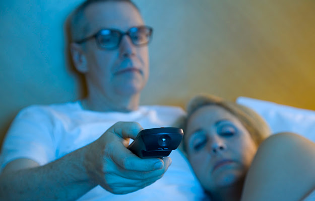 A sleepy couple watching TV in bed.