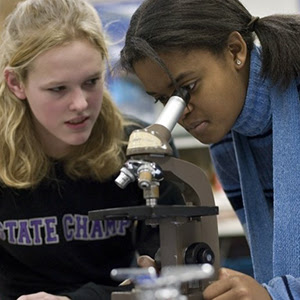 Two students working with                                           a microscope