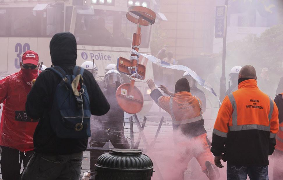 Manifestantes lanzan objetos a la policía durante una protesta convocada por la Confederación Europea de Sindicatos (ETUC) en contra de las medidas de austeridad y recortes para afrontar la crisis económica, en Bruselas.