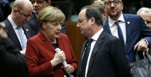 La canciller alemana Angela Merkel conversa con el presidente francés Francois Hollande antes del comienzo de la cumbre de Bruselas, en la que prevén mantener un encuentro aparte con el primer ministro griego Alexis Tsipras. REUTERS/Francois Lenoir