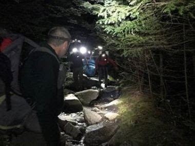 Rangers with headlamps lighting trail for rescue