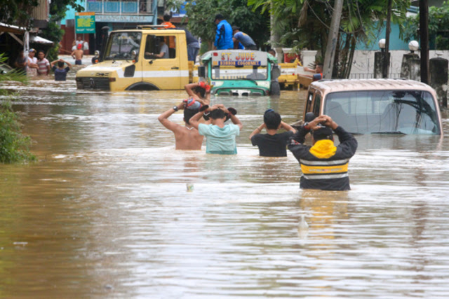 FLOODING. Police rescue residents along Kalambaguhan Street in Cagayan de Oro City as Tropical Storm Vinta lashes Northern Mindanao on Friday, December 22, 2017. Photo by Bobby Lagsa/Rappler
