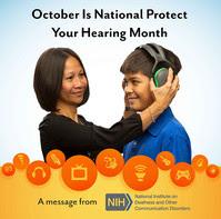 Woman placing protective earmuffs on preteen boy.