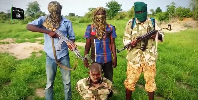 Look of horror: A Nigerian soldier is made to kneel in front of three men after he was captured by Boko Haram