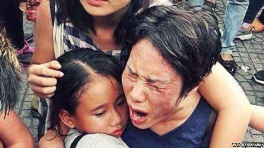 Bà Hoàng Mỹ Uyên ôm con gái trong vụ xô xát giữa lực lượng an ninh Việt Nam với người biểu tình hôm 8/5 ở Sài Gòn. Ảnh chụp màn hình.