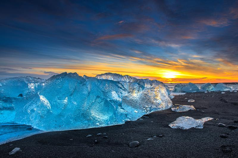 The glacier lagoon is marked by glowing skies and icy islands.