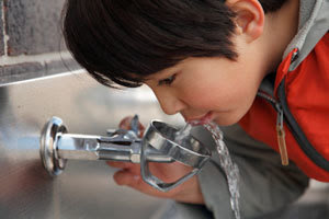 Boy drinking from water fountain
