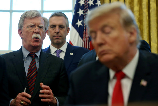"FILE PHOTO: U.S. President Donald Trump listens as his national security adviser John Bolton speaks during a presidential memorandum signing for the ""Women's Global Development and Prosperity"" initiative in the Oval Office at the White House in Washington, U.S., February 7, 2019 (photo credit: REUTERS/LEAH MILLIS/FILE PHOTO)"