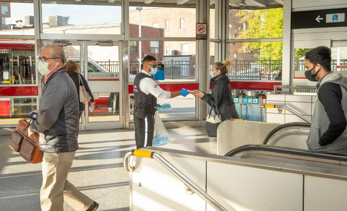 A TTC employee distributes masks to customers at Coxwell Subway Station