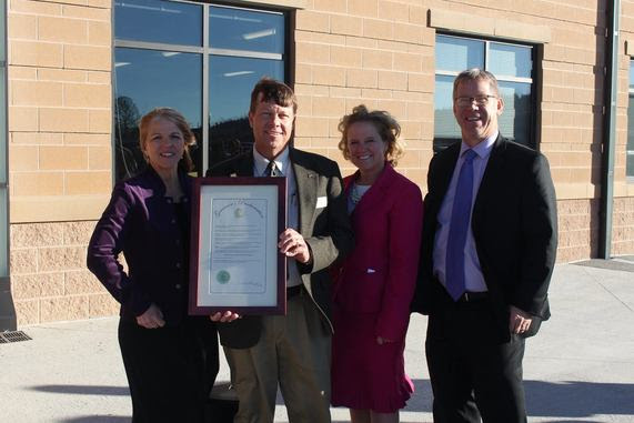 School Construction Director Del McOmie holds a proclamation from Governor Matt Mead recognizing the opening of Pine Bluffs Elementary School alongside State Superintendent Jillian Balow, the school's principal, and the district superintendent.