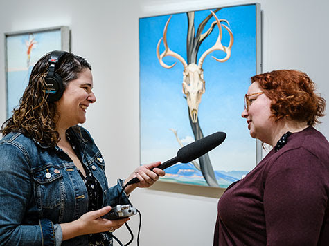 Tamar Avishai speaking with a visitor about Georgia O'Keeffe, Deer Skull with Pedernal