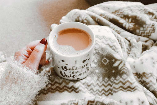 A mug of tea sat on a woman's lap with a grey fleece blanket on her knees viewed from above