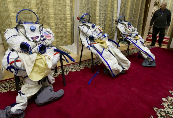 Image: The spacesuits of European Space Agency Italian astronaut Samantha Cristoforetti (R), US astronaut Terry Virts (L) and Russian cosmonaut Anton Shkaplerov (C) are prepared for their preflight training session at the Gagarin Cosmonauts' Training Centre in Star City centre outside Moscow, on December 10, 2013. All three are scheduled to blast off to the International Space Station from the Russian leased Kazakhstan's Baikonur cosmodrome in November 2014.