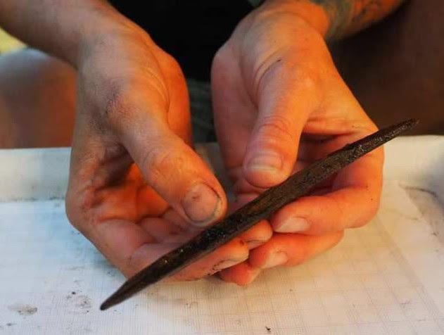 Alisha Gauvreau sostiene un artefacto tallado en madera con dos puntas de 7.000 años de antigüedad. Este artefacto podría haber sido utilizado como anzuelo para capturar peces.