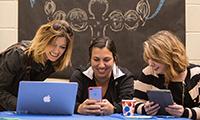 Three teachers using Apple devices (laptop, phone and iPad)