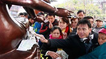 Nhét tiền vào cả tay Phật Bà nghìn mắt nghìn tay ở chùa Lim, Bắc Ninh - Ảnh Tiến Thắng
