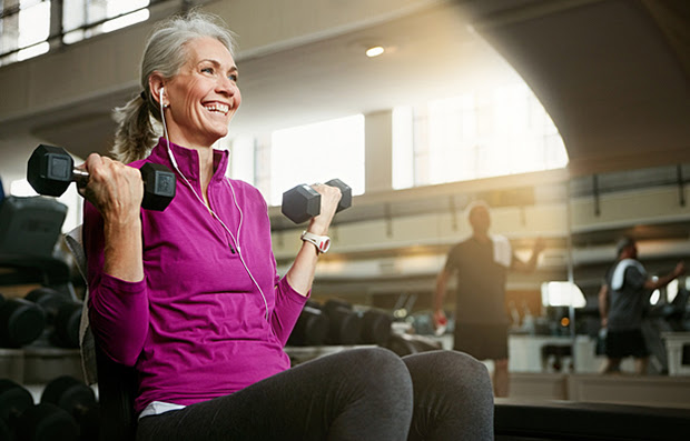 A mature woman at the gym lifting light weights.
