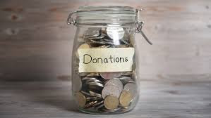 Photograph of a mason jar with a spring lid. It is full of coins and has a label made of masking tape. Handwritten is the word Donations.