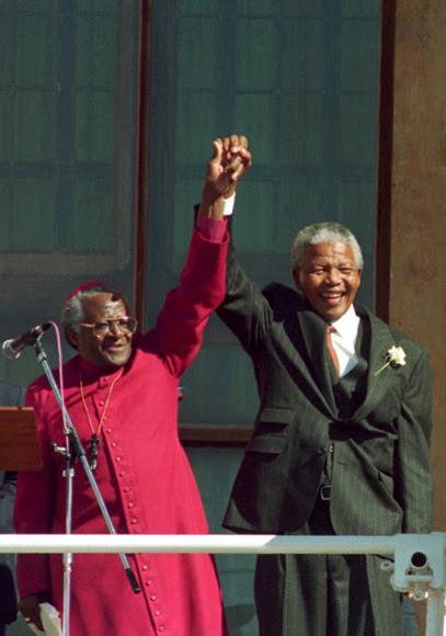 Nelson Mandela  y Desmond Tutu alzan sus manos tras la victoria en las elecciones de 1994 del Congreso Nacional Africano (CNA).