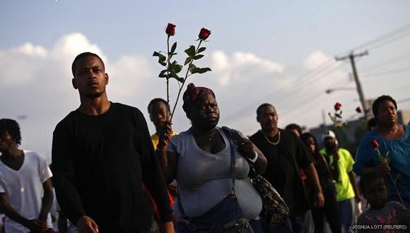 Manifestantes con rosas piden justicia por John Brown, que falleció tras recibir seis disparos de un agente.