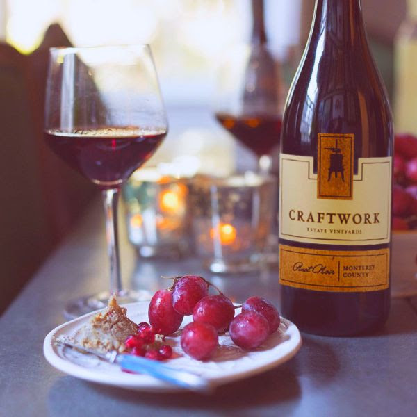 Bottle of Craftwork Estate Pinot Noir 2018 on a table with a glass of wine and a plate of grapes.