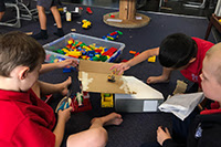 Three children playing together with lego