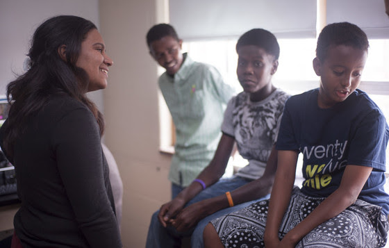 Giselle Danger-Mercaderes smiles as she talks to three boys.
