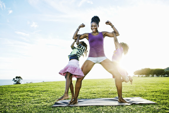 Woman exercising and playing with daughters
