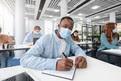 Black male student in mask at desk