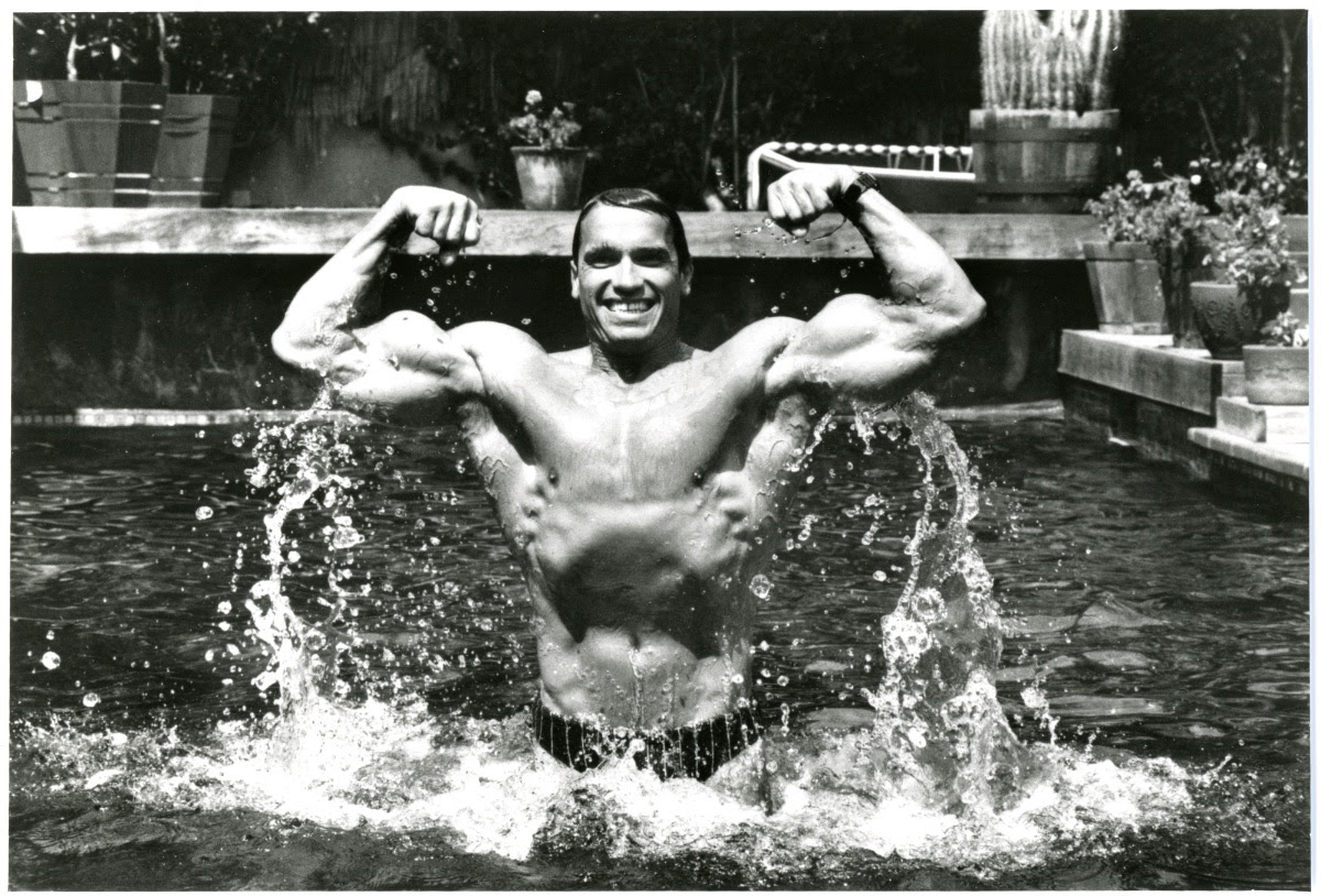 Arnold Schwarzenegger flexes as he rises out of a swimming pool