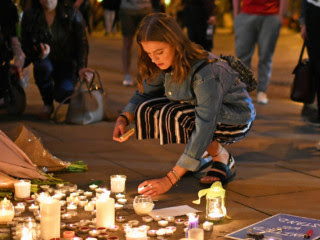A candlelight vigil in Manchester's Albert Square on Tuesday honors the victims of Monday evening's terror attack, at Manchester Arena, that killed twenty-two people and injured fifty-nine.